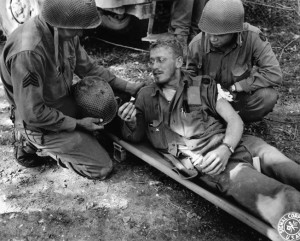 A soldier who has also been wounded in the arm and leg shows a medic the piece of shrapnel that penetrated his M1 helmet but failed to cause a potentially fatal injury.