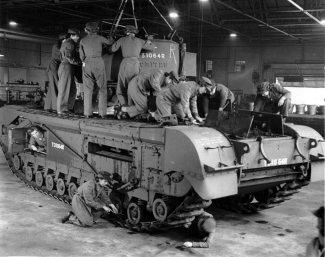 Women of the Auxiliary Territorial Service (ATS) work to guide a Churchill tank's turret into position at a Royal army Ordnance Corps depot.
