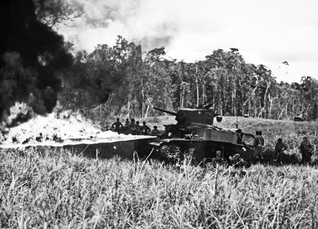 An M3A1 Stuart light tank spews a stream of fire from its bow flamethrower during a demonstration for officers from the United States, Australia, and New Zealand.