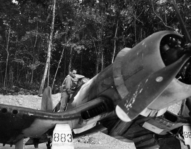 """Major Gregory """"Pappy"""" Boyington, commander of the Black Sheep Squadron, climbs atop the wing of his F4U Corsair fighter. Boyington became one of the leading aces of the Pacific War flying the Corsair."""
