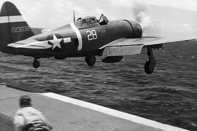 This P-47D flies off the deck of the escort carrier USS Manila Bay to attack an approaching formation of Japanese Aichi Val dive bombers east of the island of Saipan in the Marianas.