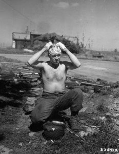 Necessity is the mother of invention for a soldier who uses his M1 helmet as a sink to wash his hair in August 1944 during a lull in the advance along the Western Front in France.