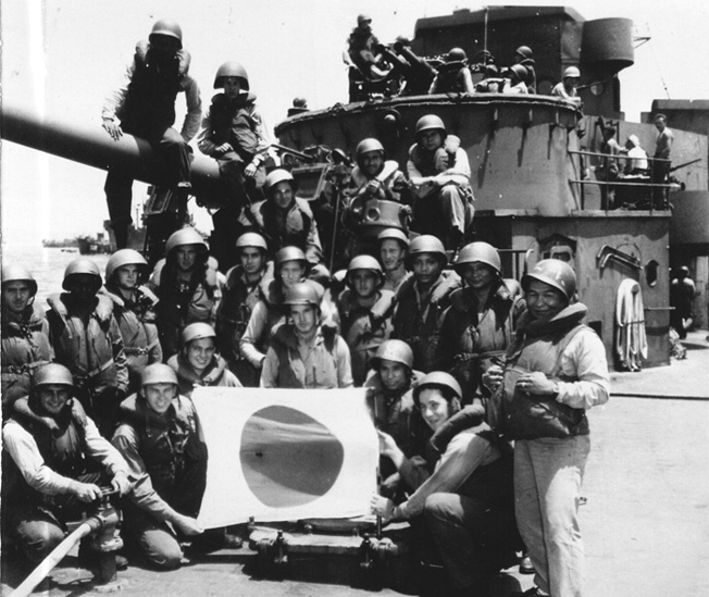Antiaircraft gun crews aboard the Taney pose with a captured Japanese flag during the Battle of Okinawa.