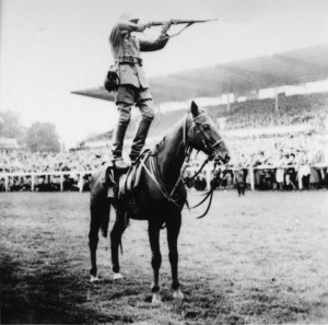 A German Army cavalryman fires his Mauser 98 bolt action rifle standing atop a horse in a prewar demonstration.