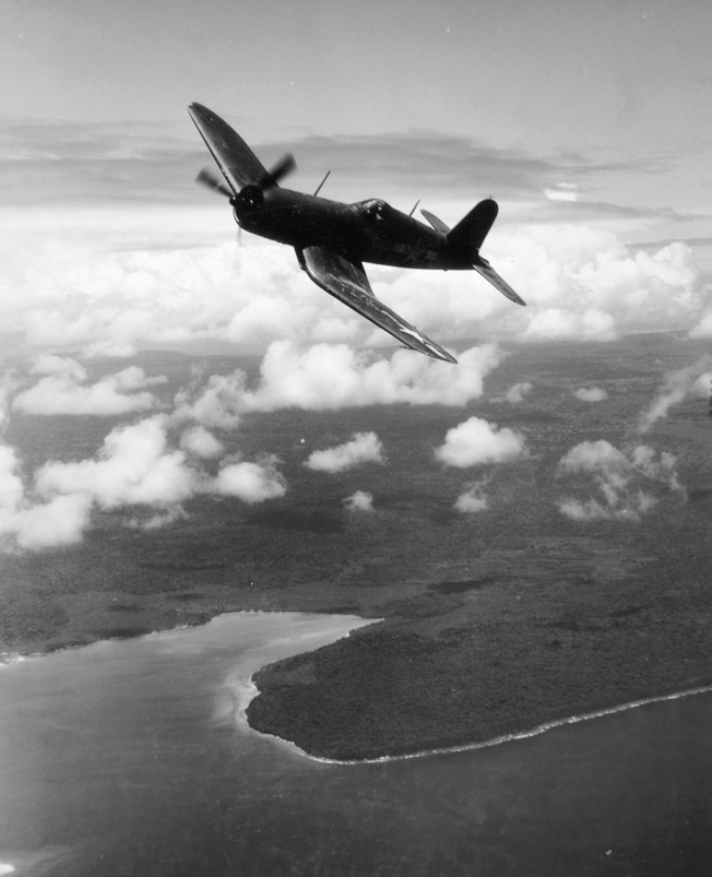 Its distinctive gull wings and the rearward location of the cockpit are readily discernible in this view of a Chance Vought F4U Corsair in flight above the island of Bougainville in 1944.