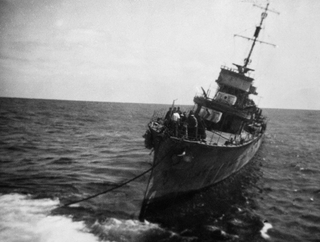 The damaged HMAS Vendetta is under tow from the former Chinese river boat HMAS Ping Wo. Vendetta was towed by Ping Wo from Java to Fremantle, Australia.