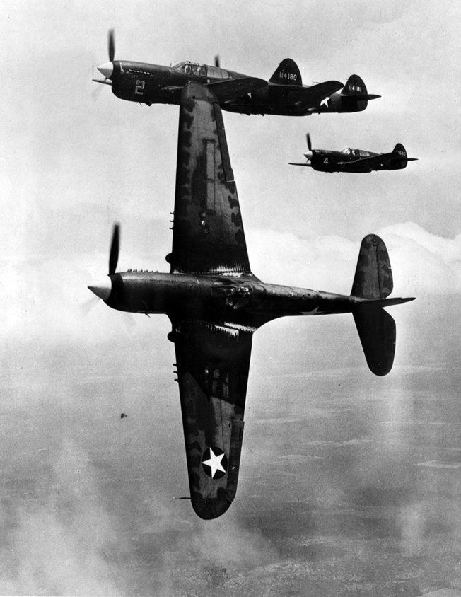 The lead plane in this formation of P-40 Tomahawks wings over to attack a formation of enemy planes. The Flying Tigers scored an impressive kill ratio against veteran Japanese pilots.