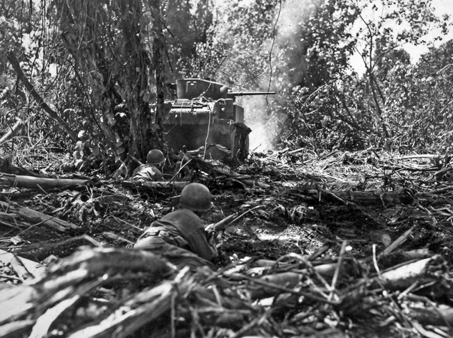 Riflemen of Company C, 132nd Infantry Regiment take up positions behind a Stuart light tank of Company A, 754th Tank Battalion during the Hornet's Nest fighting on Bougainville.