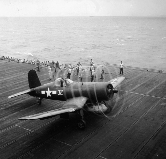 On February 27, 1945, a Marine Corps F4U Corsair revs its engine for takeoff aboard an Essex-class aircraft carrier. A pair of Marine fighter squadrons and their Corsairs had been assigned to ship-borne duty only days earlier.