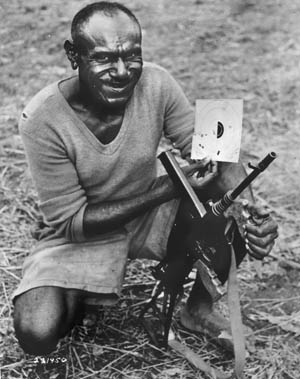 A Papuan native who has entered service with Allied forces displays his target after hitting 11 out of 15 rounds with his Owen gun from a distance of 30 yards. The Owen gun remained in service with Australian soldiers until the 1960s.