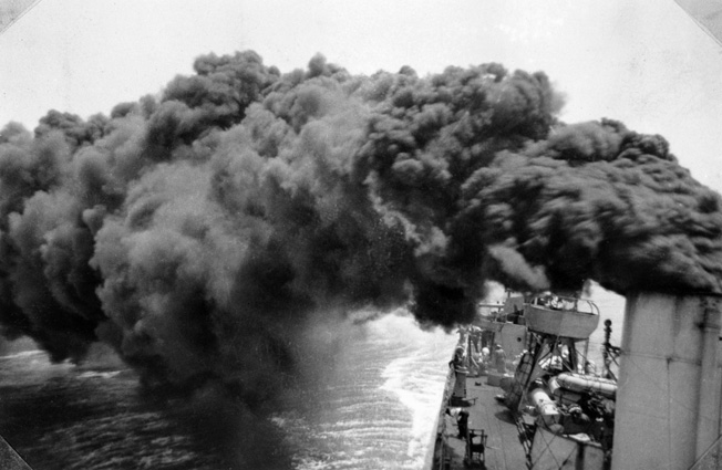 Black smoke belches from a stack aboard HMAS Vendetta as the destroyer makes a smokescreen during service in the Mediterranean.