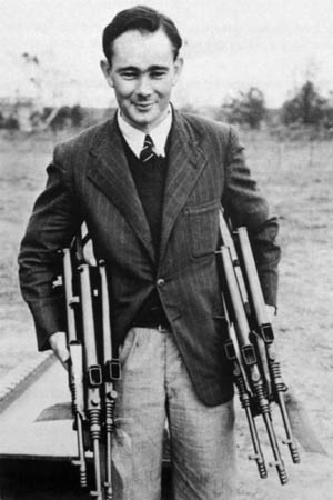 Evelyn Ernest Owen displays examples of his  Owen gun, which was criticized in some quarters but nevertheless entered production in Australia.