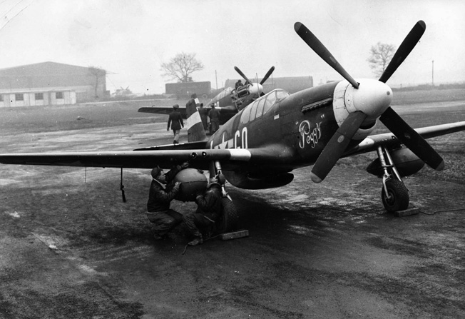 On a muddy airfield in England, P-51 Mustangs sit ready for their pilots to climb aboard as two ground crewmen make a final check of an external drop tank. The extra range provided by the drop tanks allowed the fighters to escort bomber formations deeper into Germany.