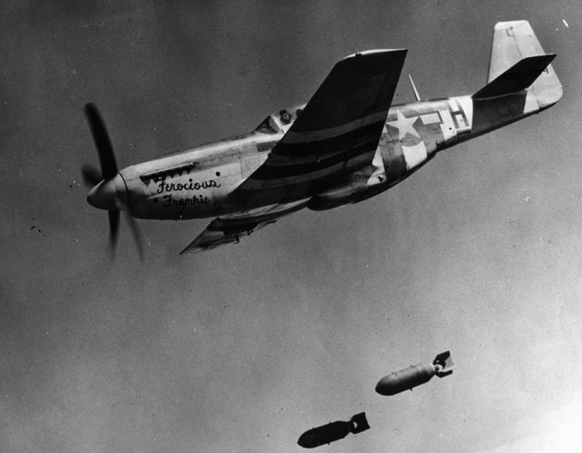 """During a fighter bomber mission, Lieutenant Colonel Wallace Hopkins of 8th Fighter Command releases his bomb load from his P-51 Mustang nicknamed """"Ferocious Frankie."""" The Mustang proved capable in both the escort and ground attack roles."""