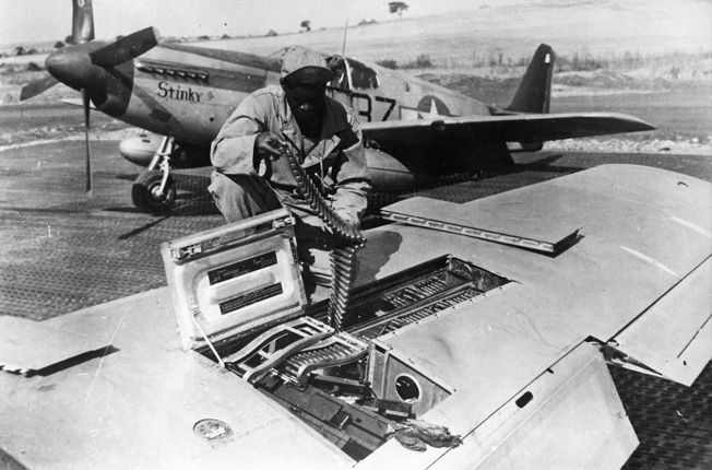 A Fifteenth Air Force armorer loads a belt of ammunition for one of a Mustang's six .50-caliber machine guns. Flying from its base in Italy, this fighter plane was being readied for a mission over Germany. Often, when escort duties were completed, the Mustangs were allowed to seek targets of opportunity.