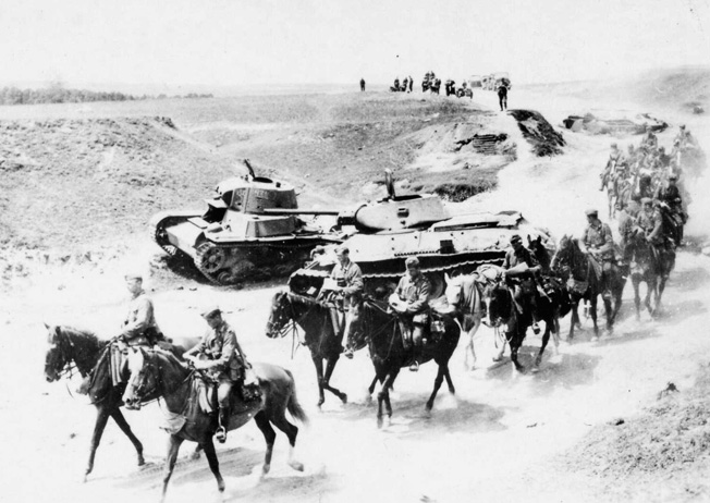 During the spectacularly successful Wehrmacht offensive of 1941, German mounted infantrymen advance past Soviet tanks that were knocked out in earlier combat. Later, the horses would suffer greatly during the terrible Russian winter.