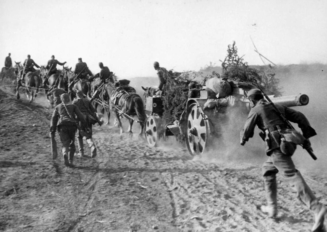 A team of horses strains under the weight of a heavy artillery piece, which produces a cloud of choking dust as German soldiers advance alongside. Note the makeshift attempt to camouflage the gun.