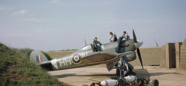 Ground crewmen service a Hawker Typhoon of RAF No. 175 Squadron near Colerne. Dummy bombs are shown in the foreground for practice loading on the plane's underwing racks.