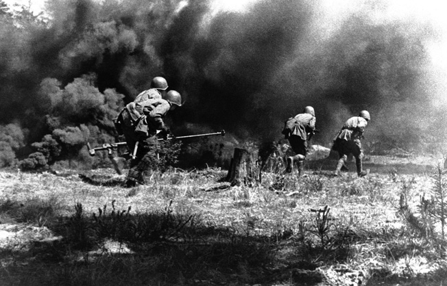 Following two infantrymen armed with conventional rifles, a two-man PTRD-41 antitank team rushes into combat as smoke from exploding shells billows nearby. By the summer of 1943, more than 1.5 million antitank rifles had been produced in the Soviet Union.