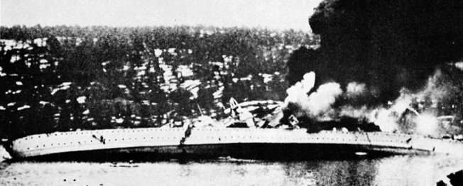 A mass of smoke and flames, the German heavy cruiser Blücher victim of Norwegian land-based artillery, rolls over and begins to sink during the invasion of Norway,