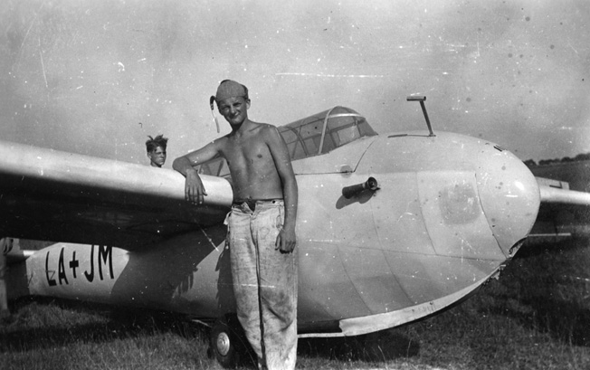Dulias poses in front of a two-seater Olimpia Kranich soaring plane after a solo flight in the summer of 1944.