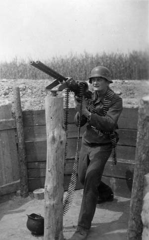 With a belt of ammunition around his neck, Dulias dons a Luftwaffe flak helmet and mans a double-barreled machine gun (MG 81) which has been mounted on a post for gunnery training.