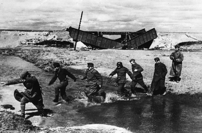 Under the watchful eye of a single Red Army infantryman, a group of German prisoners passes a demolished railway bridge and splashes across a small stream on the Eastern Front.