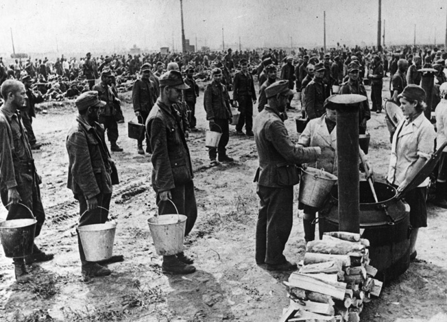 During transit to an internment camp, German prisoners line up to receive a meal from a Red Army field kitchen near Moscow in July 1944.The sheer number of German prisoners needing food and shelter stretched Soviet resources. Note that two of the cooks are women.