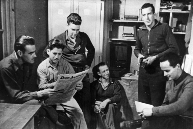 In this staged photograph, captured American airmen peruse a German newspaper in Stalag Luft III. In reality, the conditions in German POW camps were harsh at best. The situation deteriorated rapidly as the Allied armies advanced into Germany.