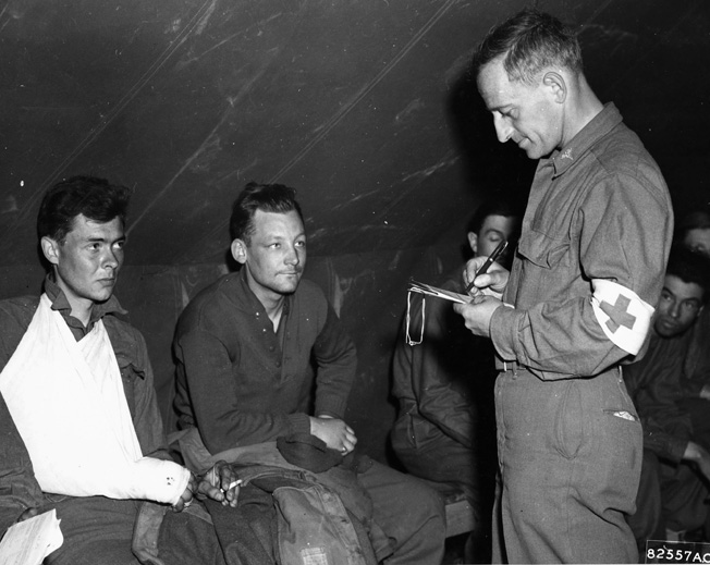 On April 27, 1945, liberated prisoners of war have their identification checked by members of the U.S. Army Medical Corps. The former POWs were then evacuated by aircraft of the 9th Troop Carrier Command.