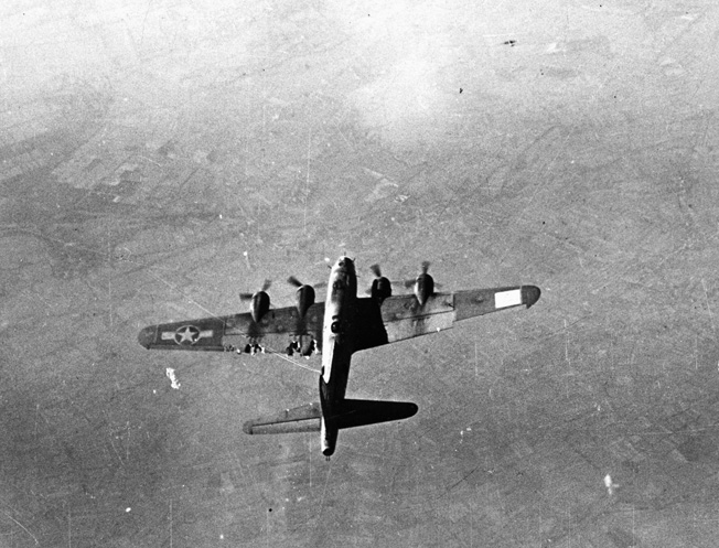 Having sustained visible damage to its left wing either from thick German flak or marauding Luftwaffe fight- ers, this B-17 bomber nevertheless maintains formation during the bombing run on a mission against the communications center of Gelsenkirchen, Germany.