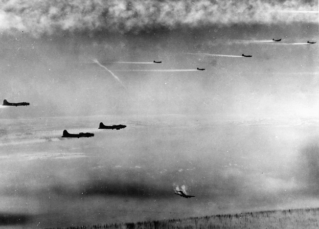 A photographer of the Eighth Air Force captured this haunting image of a B-17 streaking earthward as smoke streams from its engines while the remaining bombers in the frame continue toward their target, the city of Bremen. The tail assembly of the stricken B-17 has apparently been shot away.