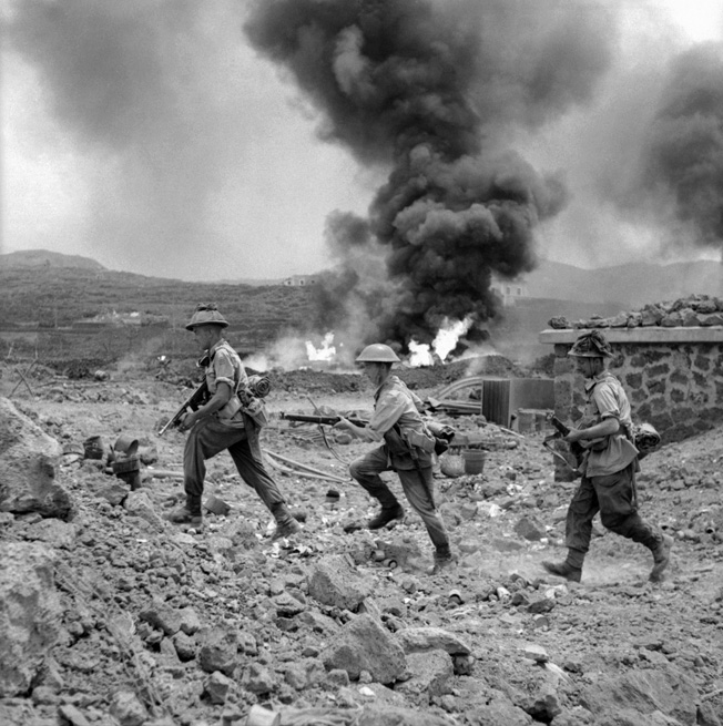Soldiers of the 1st Battalion, Duke of Wellington's Regiment, rush past a burning fuel storage depot as they secure the island of Pantelleria.