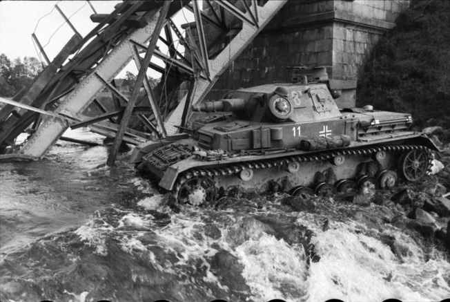 After the retreating Soviets have destroyed a bridge across a stream near the coast of the Baltic Sea, this German tank of the 8th Panzer Division fords the waterway in July 1941.