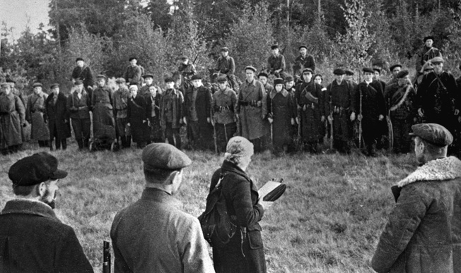 ORIGINAL: The Great Patriotic War of 1941-1945. One of the guerrilla teams in Pskov region. Young Communist Shura Pavlova is swearing. 1941.