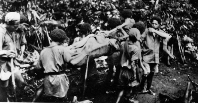 A wounded Australian soldier is painfully transported toward an aid station on New Guinea by native porters. Friendly natives who knew the jungle and were willing to assist the Allies played a key role in the eventual victory.