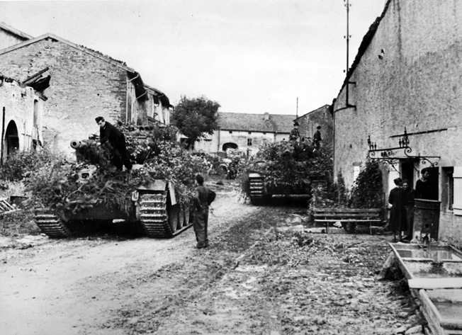 Camouflaged against a potential Allied air attack, a German armored vehicle moves into position in a village along the Moselle River. This photo was taken in October 1944, and by that time German forces had been decimated during the rapid summer advance of the Allies.