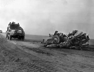 Wheeled vehicles of the U.S. 4th Armored Division speed past a destroyed German artillery piece and the dead crew sprawling beside it. German troops and equipment that dared to move in daylight were often the targets of Allied fighter-bombers, which wreaked havoc and caused heavy casualties during the final months of the war in Europe.