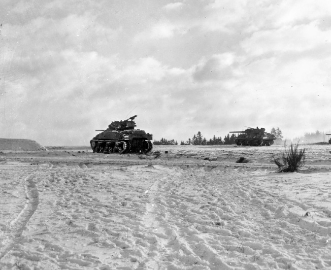 During the Battle of the Bulge in December 1944, an American Sherman tank, accompanied by an M10 tank destroyer, advances steadily across open ground. Such terrain was dangerous, as German antitank teams and hidden guns lurked along the edges of fields and roads.