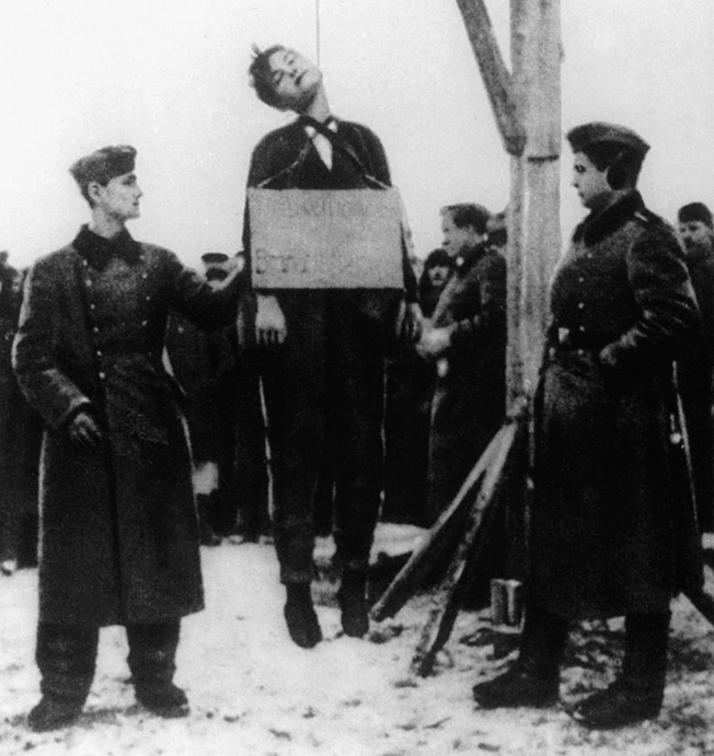 Zoya Kosmodemyanskaya hangs lifeless after being executed by the Germans in reprisal for partisan attacks.
