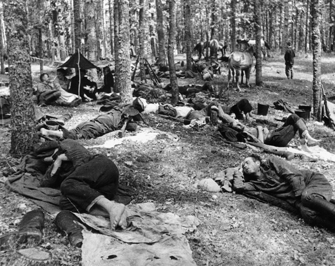 During a respite from fighting with Germans in Poland, Soviet partisans find temporary rest at their woodland encampment, 1944.
