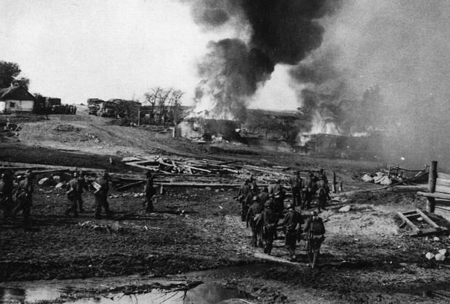 Advancing toward the smoldering ruins of a Russian village, German soldiers prepare to search the remains of buildings for evidence of partisan activity. The German troops were encouraged to act brutally against the civilian population.