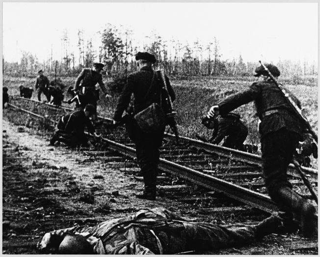 After killing the German sentries who guarded this rail line, Soviet partisans plant mines. Partisan attacks were a constant worry for the Germans on the Eastern Front.