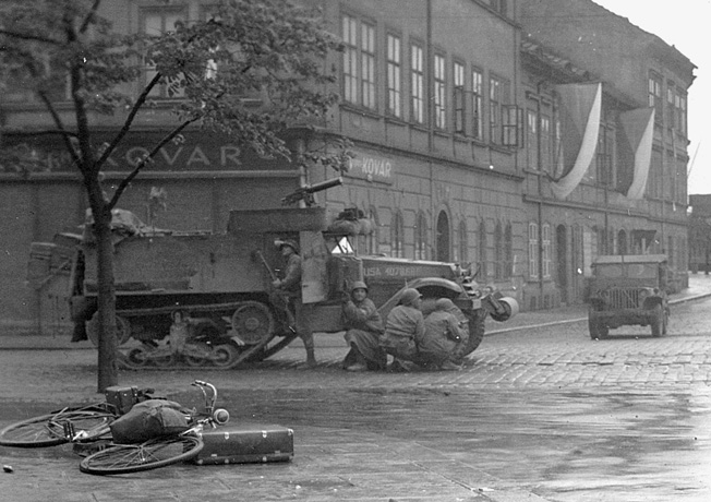 Third Army soldiers pile out of a half-track to search for a German sniper. As German resistance began to crumble, the American found themselves fighting lone snipers and children with antitank weapons.