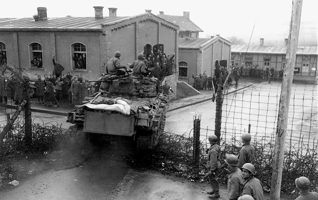 A Sherman tank smashes through the gate of the POW camp at Hammelburg as American and British soldiers wave and celebrate.