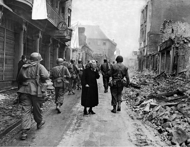 Third Army soldiers march past a German woman in Frankfurt am Main on their way to Czechoslovakia.