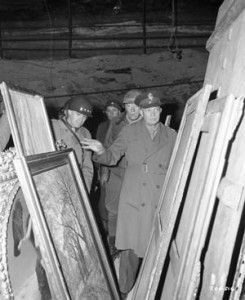 General Omar Bradley (far left), Patton, and Dwight D. Eisenhower examine precious paintings in the Merkers salt mines Patton's assistant, Charles Codman, can be seen in the background.