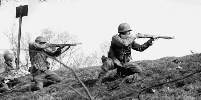 Germany: Infantrymen of the 302nd Infantry Regiment 94th Division, KK Corps, 3rd U.S. Army, fire at enemy positions across the Rhine River near Mannheim Germany. March 21, 1945  ©Topham / The Image Works
