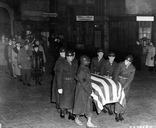 General Patton's wife, Beatrice, follows his casket through the train station in Luxembourg City en route to the nearby cemetery in Hamm.