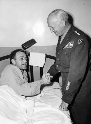 General Patton visits his son-in-law, Lieutenant Colonel John Waters, while the latter recuperates in Walter Reed U.S. Army Hospital in Washington, D.C. Waters had been held in a German prison camp for three years. Patton was reported to have attempted a rescue operation at one time.